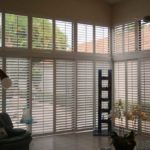 A large tiled living room that has full wall windows with plantation shutters over looking the pool