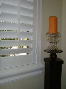 White plantation shutters with a tall wooden candle stand displaying a orange candle