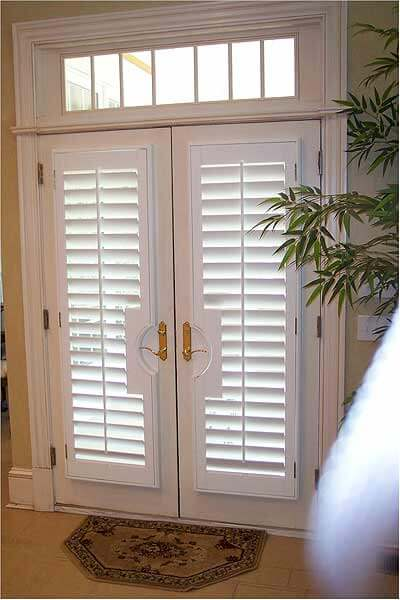 A double entry door with gold fixtures and white custom plantation shutters