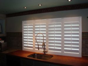 A kitchen with a single sink with white plantation shutters