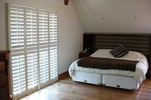 white wood plantation shutters in bedroom with wood foors