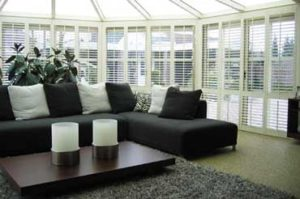 A dark grey couch with grey and white pillows with white custom wood plantation shutters in the background