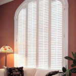 A large arched custom plantation shutter window that has white shutters and a wide trim moulding with hinges on each side