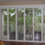 Six full length custom plantation shutters in white in a spacious bedroom that has bisque beige walls