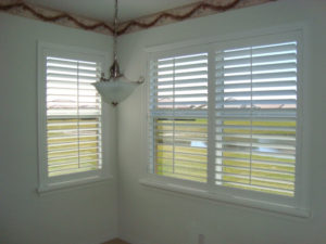 One large window and one small window with white plantation shutters open and overlooking a pond